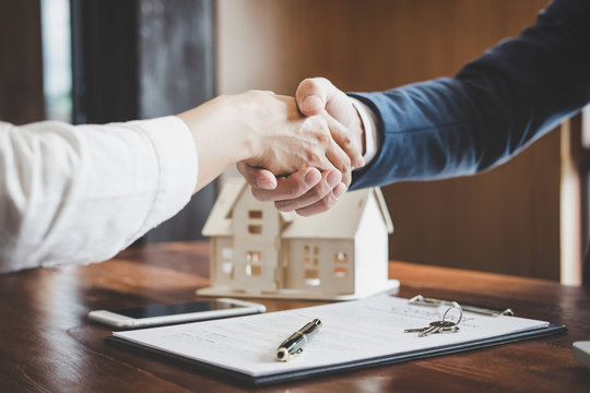Estate agent and customer shaking hands after finished contract after about home insurance and investment loan