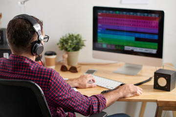 Rear view of young sound producer working with computer and composing a music