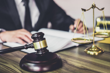 Judge gavel with Justice lawyers, Gavel on wooden table and Counselor or Male lawyer working on a documents at law firm in office. Legal law, advice and justice concept