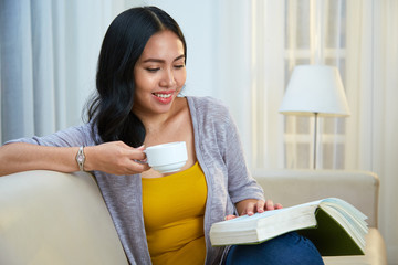 Lovely Filipino female with charming smile enjoying fresh hot drink and reading nice book while sitting on comfortable couch in cozy living room