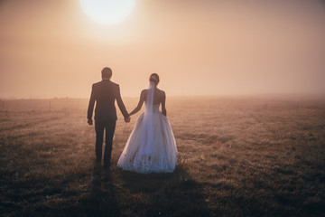 Bride and groom walking together in romantic autumn morning