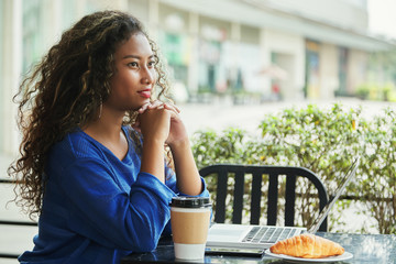 Side view of charming Indonesian female smiling and thinking while sitting at table in outdoor cafe near modern laptop and snack