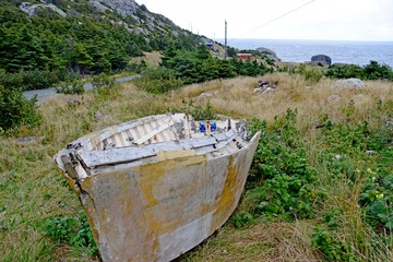 deteriorating dory fishing boat on land in  a meadow  at Biscayan Cove, a  abandoned fishing village along the East Coast , Avalon Peninsula, NL Canada