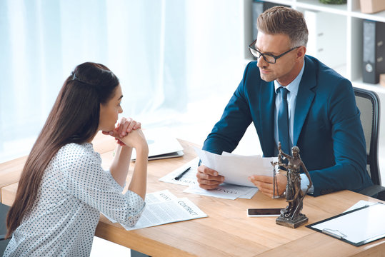 high angle view of lawyer and client looking at each other while discussing contract in office