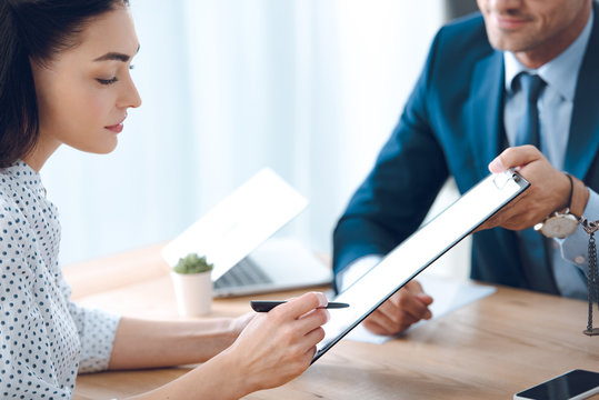 cropped shot of lawyer holding clipboard and young woman signing document