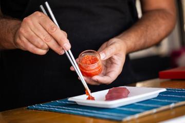 Crop man serving caviar for tuna