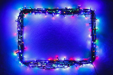 Christmas lights frame on snow background, blue and purple color