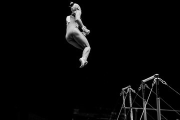 women gymnast flips dismount in uneven bars black and white photo