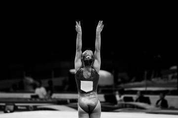 back female gymnast beginning of performing black-and-white photo