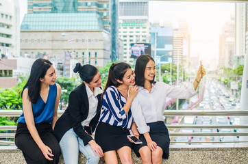 Four happy Asian businesswoman colleague taking selfie with smartphone in city,looking at camera, happy healthy diverse fit people relaxing after working out together in office.