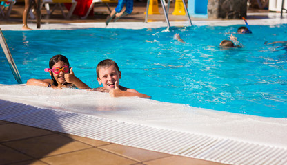 Little boy and girl with pink goggles smiling with thumbs up by swimming pool edge. Young kids having fun on summer holidays. Resort leisure time, travel vacation, hotel activity, tourism concepts