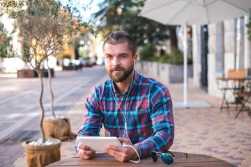 Handsome hipster guy working on digital tablet.