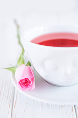 Fruit tea in white cup and pink rose on a white background. Free space