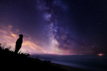 Silhouette of a lonely man watching the stars and the Milky Way over the sea in Tuscany Fototapete