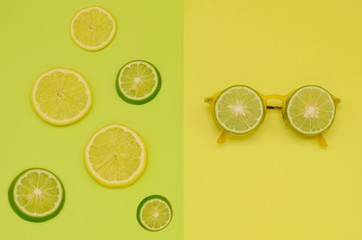 Sliced lemon and lime isolated on green color background and yellow sunglasses that have green limes put on it isolated on yellow background for summer time.
