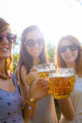 Group of young women enjoying outdoors with beer.