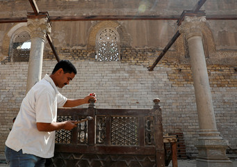 An Egyptian worker carries out restoration work inside al-Zahir Baybars Mosque, an architectural landmark in old Cairo