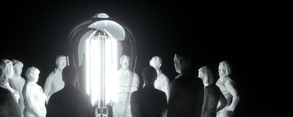 Ein Team von Mitarbeitern schaut auf eine leuchtende Glühlampe