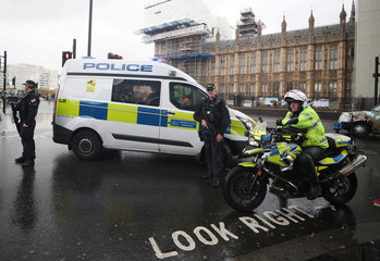 Armed and motorcycle police officers stand next to the Houses of Parliament after an area of the Victoria Embankment was cordoned off, in London
