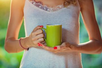 Girl drinking coffee / tea in the garden.