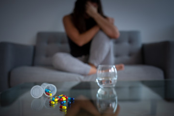 Depressed woman on a couch with medication pills and a glass of water