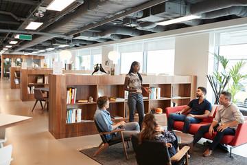 Casually Dressed Businessmen And Businesswomen Having Informal Meeting In Modern Office