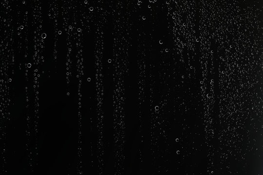 black wet background / raindrops for overlaying on window, concept of autumn weather, background of drops of water rain on glass transparent