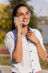 Young woman using mobile phone in the park by river