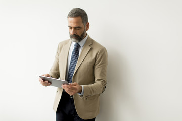 Handsome senior businessman with digital tablet by wall