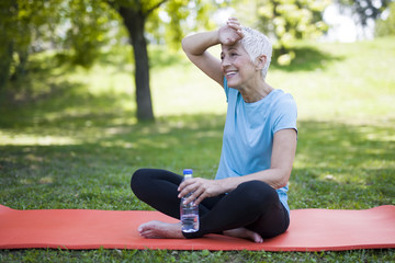 Senior woman resing after workout in park