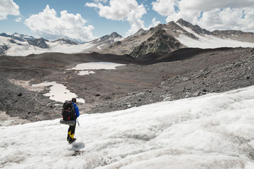 Traveler in a cap and sunglasses with a backpack on his shoulders in the snowy mountains on the glacier against the sky and clouds. Traveler in a natural environment