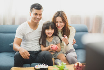 Family time young Parents and Daughter laughing which sit on sofa, daughter take an apple on hand which sit between father and mother and looking TV at home