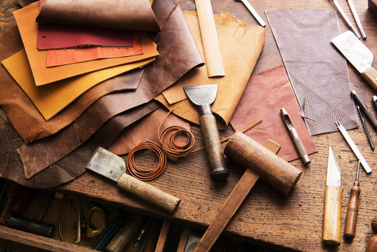 Leather craft or leather working. Selected pieces of beautifully colored or tanned leather on leather craftman's work desk .