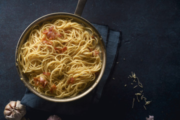 Italian pasta carbonara with bacon in a pan on dark background