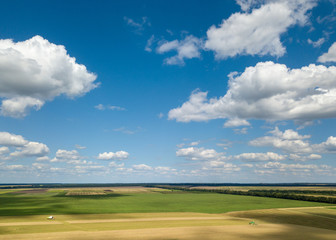 Wall Mural - Panoramic view from the drone of beautiful landscape of agricultural fields with harvesting on the background of the blue cloudy sky at sunset.