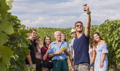 group of tourists take a selfie outdoor in the vineyard during a lesson about growing wine