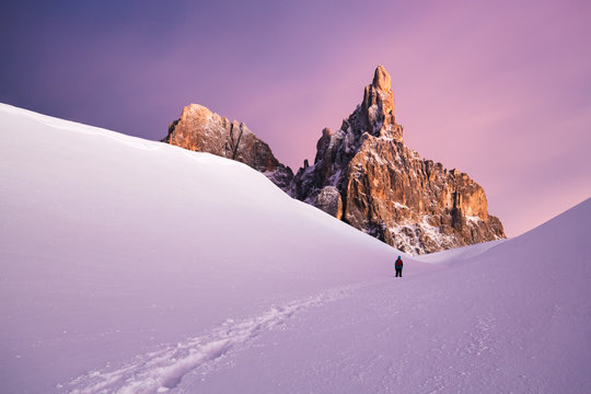 Man walking through snow covered path with mountains in the background