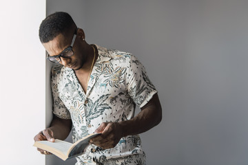 Smart ethnic man in glasses reading book