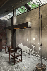 Altar and huge cross in a church or chapel destroyed by fire of a candle. Remains of burned religious place with sunlight passing through the windows.