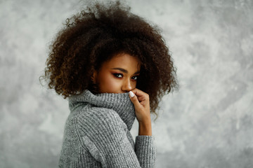 Portrait of young african american woman with an afro hair wear high-neck wool and cashmere sweater, hiding her mouth under the golf Wall mural
