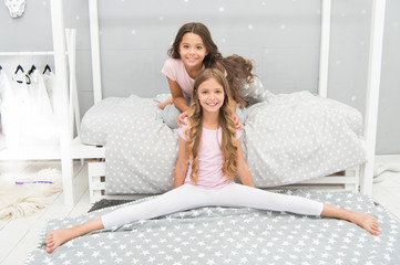 Stretching daily regime. Gymnast practice split with friend. Girl child sit split in bedroom. Friends gymnasts support each other. Sport lifestyle. Girl kid pajamas stretching. Stretching exercise
