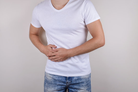 Cropped close up photo portrait of unhappy sad upset guy holding touching right side wearing casual t-shirt denim trousers isolated grey background