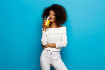 Wall Mural - Beautiful african american girl drinking orange juice