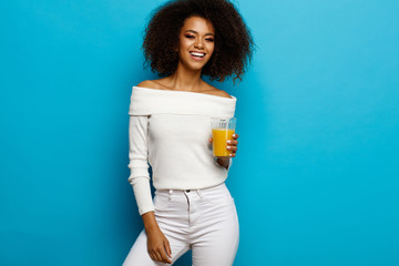 Wall Mural - Beautiful smiling african american girl with a glass of orange juice