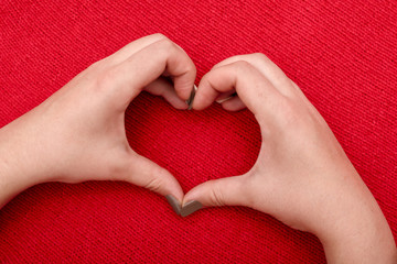 Beautiful heart of women's hands on a red knitted background