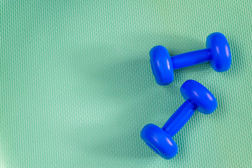 little blue dumbbells against a bright background