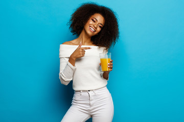 Wall Mural - Beautiful smiling african american girl showing a glass of orange juice