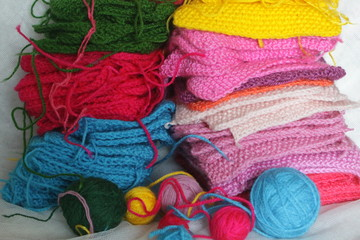 Piles of knitted colorful patches and balls of yarn.