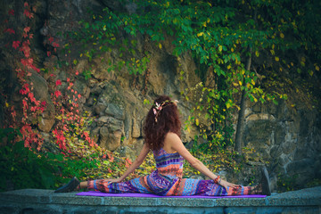 young woman practice yoga spaga pose outdoor colorful autumn background