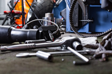 Row of screws and wrench tools on a floor in workshop near repaired old bike or motorcycle engine. Industrial scene with equipment